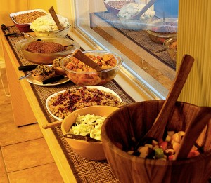 From near to far: fruit salad, cole slaw, pomegranate quinoa, squash and bean stew, stuffed squash, Vegan Turkey Roast, mashed potatoes, and green bean casserole. Not shown: nog, fruit juice, pumpkin pie, apple pie, vegan ice cream, vegan frozen yogurt, vegan whip cream, and chocolate coconut cookies. (photo by Judith Lautner)