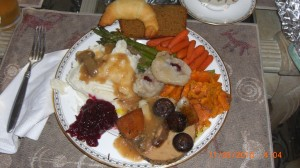 tofurky with baby bella mushrooms and vegetarian gravy, mashed cauliflower and potatoes with gravy, cranberry sauce, honey glazed carrots, ginger baked sweet potatoes, asparagus with soy butter, vegan pumpkin bread, a crescent roll, and the vegan dumplings that come with the tofurky, courtesy of http://scottpageazyoga.com/blog/?p=477